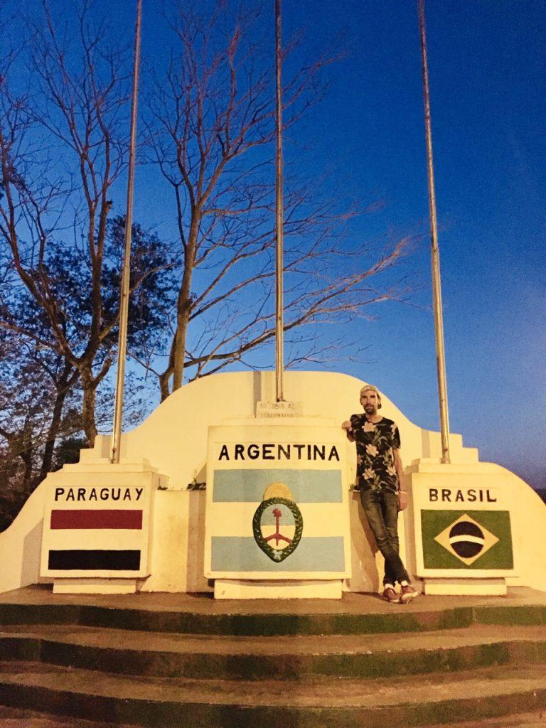 Homme devant drapeaux argentin brésilien et paraguayen à Iguazu